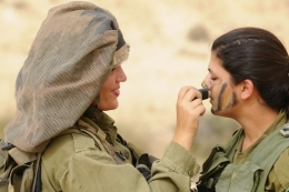 Women putting on combat makeup